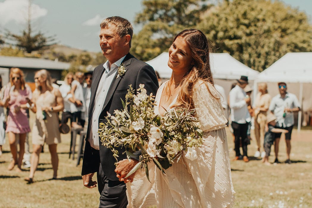 Nicole and Choppie - Gisborne Wedding captured by Oriwia Soutar. Free spirit in her Daughters of Simone gown; a seventies silhouette, fluted sleeves. Bohemian bride. Featured on Wild Hearts, New Zealand. Wild Flowers.
